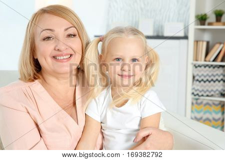 Cute happy girl with grandmother sitting on sofa at home