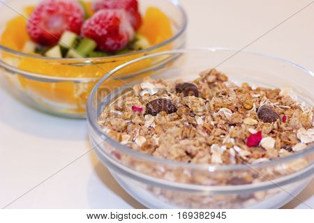 glass bowl with pieces of fresh fruit - kiwi orange and frozen strawberries and bowl with baked crunchy muesli