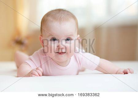 Cute baby wearing lying on tummy in nursery room