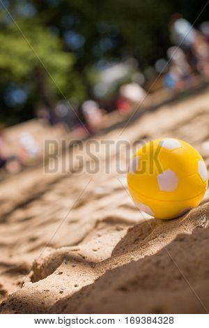 Yellow ball on the sand in the park on a sunny summer day. SUmmer holidays