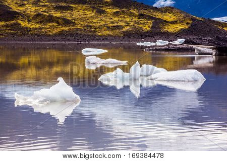 The picturesque cold lake with splinters of ice floes formed by thawed snow of grand glacier Vatnajokull.  Summer in Iceland. The concept of extreme northern tourism
