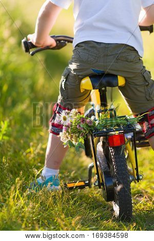 Close up of little kid boy riding on his bicycle with flowers outdoors. Boy riding his first yellow bike on a meadow. Leisure activities for children outdoors. Summer time. Happy summer concept