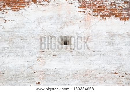 A fragment of the ancient fortress wall with a small sight window of the Novodevichy convent. Peeling white plaster on red brick