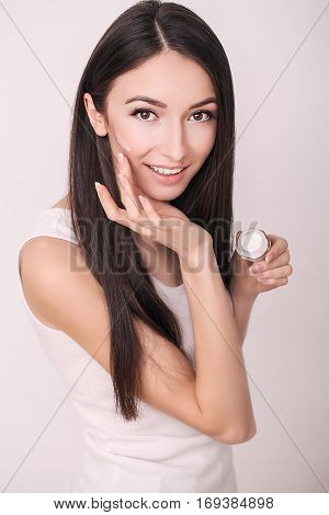 Face Treatment. Woman in Beauty Salon. Applying cosmetic cream. A beautiful young woman applying face moisturizer. Scine care of the face and hands.