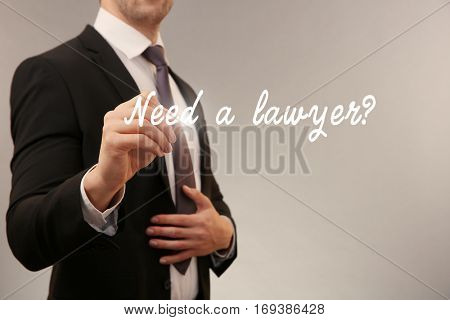 Man writing text NEED A LAWYER? on virtual screen