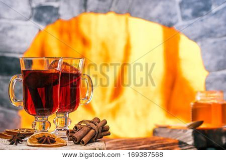 Pair of mulled wine glasses on the rustic board. Hearth background