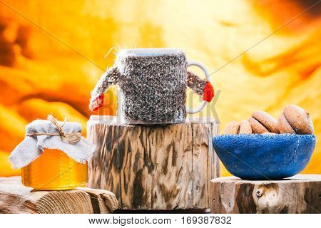 Tea mug in sweater, cookies and honey jar on rustic wood stands
