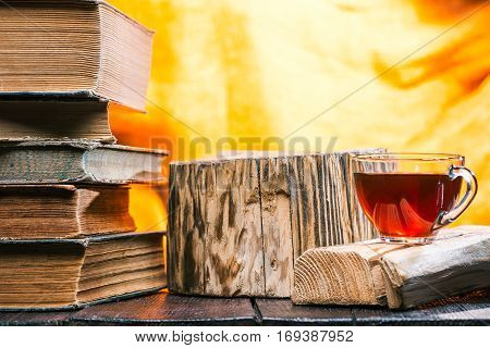 Cup of tea on rustic wood board. Stack of old books next to tea