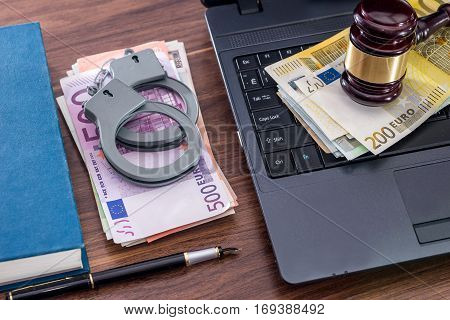 Wooden Hammer, Handcuffs And Euro Bills, Laptop On Desk.