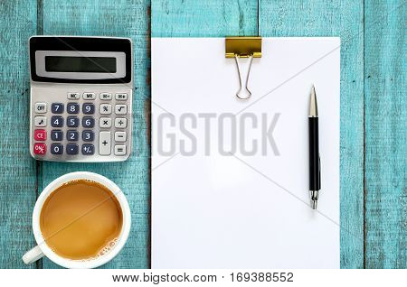 Blue Wooden Desk Table With Paper Ream, Pen, Calculator And Cup Of Coffee.