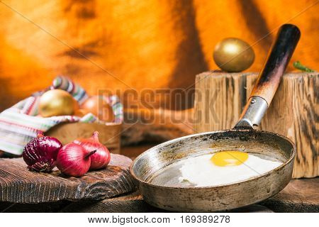 Fried egg on frying pan. Red onions on rustic cutting board. Golden eggs on the background