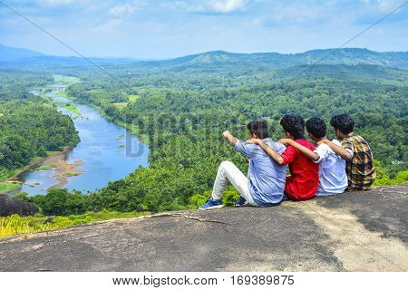 Happiness summer friendship concept. Group of friends spending time together having fun outdoor looking on river back view