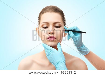 Plastic surgery concept. Doctor drawing marks on female face against blue background