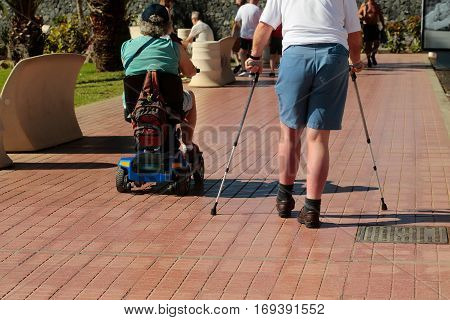 Disabled Men Walk On Promenade