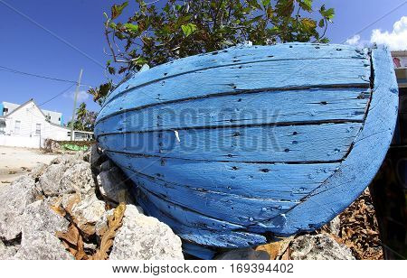 Bright blue old wooden boat hull on rocks, green tree and blue sky in background