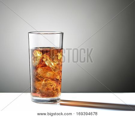 Cold glass of iced tea with ice cube isolated on a gray background