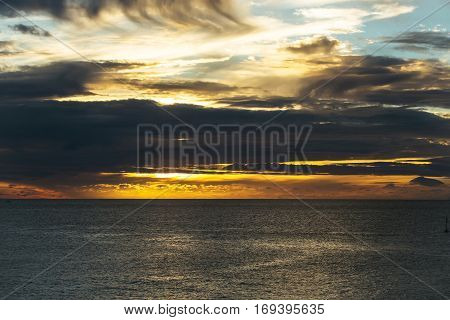 Dramatic evening sky with dark clouds over sea or ocean water surface after sunset in blue grey and orange colors on overcast background