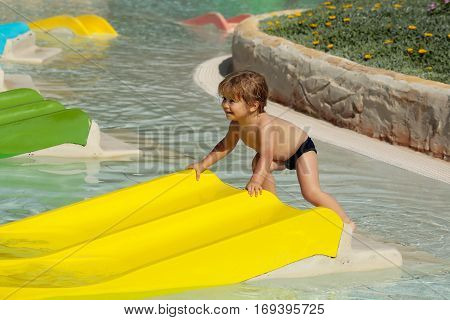 Happy Cute Baby Boy Plays On Yellow Waterslide