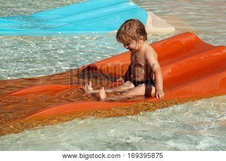 Happy Cute Baby Boy Slides From Orange Waterslide