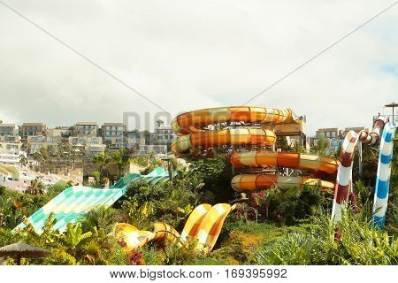 Beautiful water or aqua park with colorful waterslides in green tropic garden outdoors on summer day on white sky background
