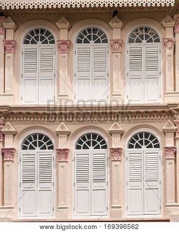 Pink, ornate building facade, in China Town, Singapore, Asia, with detailed archways and shutters for each window