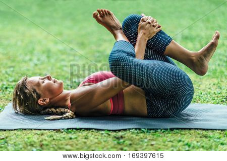 Young woman doing Yoga reclining position, toned image