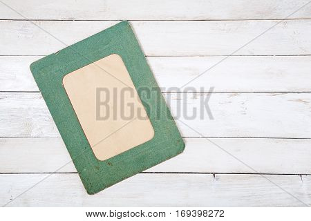 Retro green photo frame on white wooden background. Top view