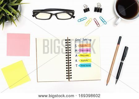 Smart goal setting on spiral notebook with pen pencil office supply eye glasses and coffee cup over white desk table background Business success concept