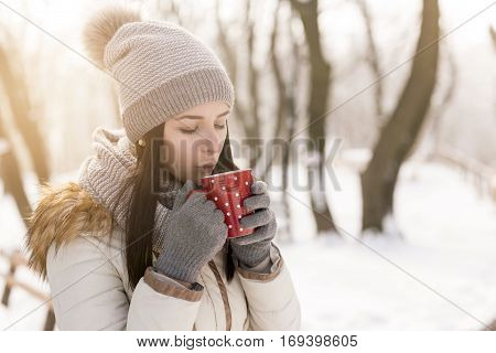 Beautiful young woman wearing warm winter clothes standing outdoors and drinking a cup of hot tea enjoying snowy winter day