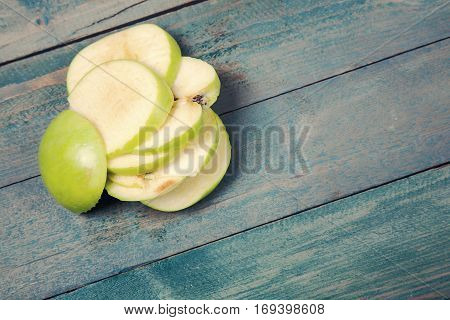 Heap of ripe apple slices on old wooden table. Top view