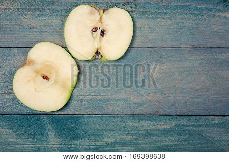 Two of ripe apple slices on old wooden background. top view