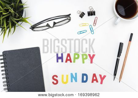 Office desk table with supply pen pencil notebook computer eye glasses sticky note cup of coffee and happy sunday word on white background