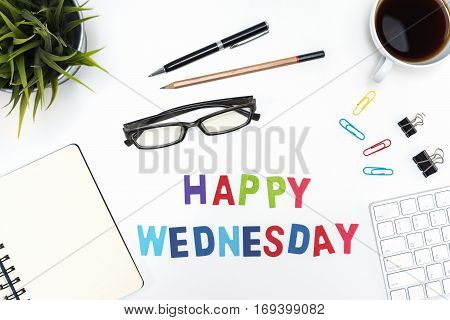 Office desk table with supply pen pencil notebook computer eye glasses sticky note cup of coffee and happy wednesday word on white background