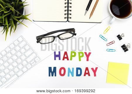 Office desk table with supply pen pencil notebook computer eye glasses sticky note cup of coffee and happy monday word on white background