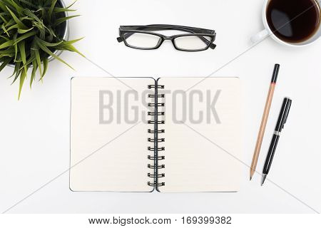 Open spiral blank notebook with pen pencil eye glasses cup of coffee and small flower plant on white desk table background flat lay top view