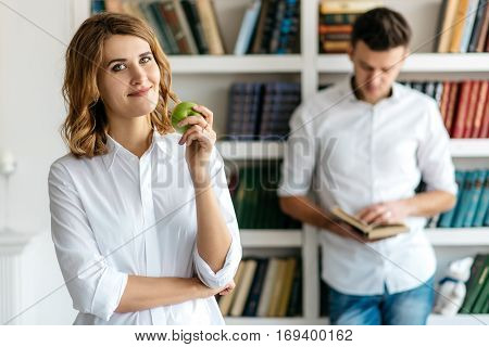 Young man and woman in white shirts standing in a library. Woman holding an apple and looking at the camera. Behind the man reading a book. Many shelves with book  on a blurred background
