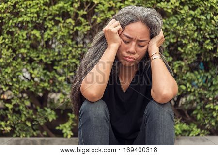 Unemployment woman and gray hair with worried stressed face expression looking down