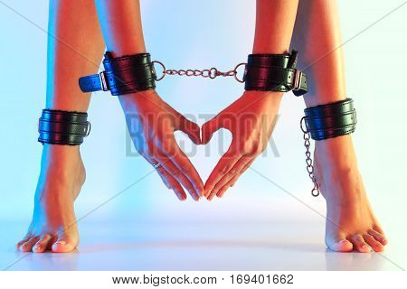 Sexy long female legs barefoot on tiptoes in leather cuffs and hands in leather cuffs chained together fingers make form of heart against colorful texturized background horizontal view