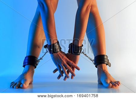 Sexy long female legs barefoot in leather cuffs and hands in leather cuffs chained together against colorful texturized background