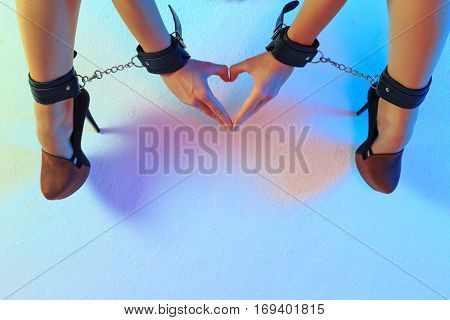 Sexy long female legs in high heel shoes and leather cuffs chained together with hands in leather cuffs fingers make form of heart against colorful texturized background horizontal view