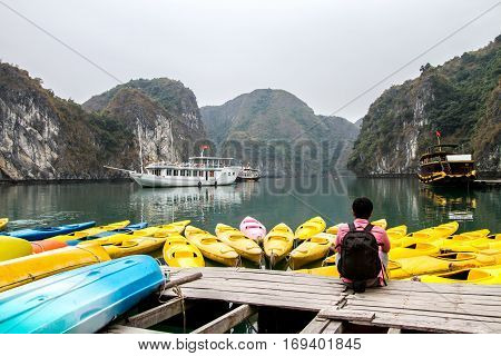 Traveler Man relaxing meditation in halong bay and enjoy the beauty of seascape and mountain