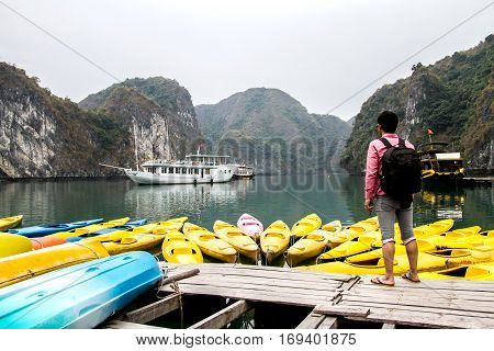 Man traveler relaxing meditation in halong bay and enjoy the beauty of seascape and mountain