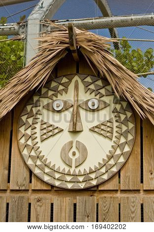 Traditional Maori art work on a wooden building, with a thatched roof