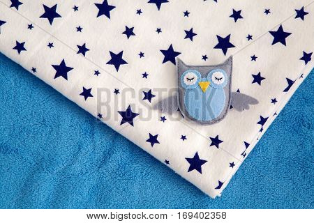 toy owl rests on a child's diaper with stars