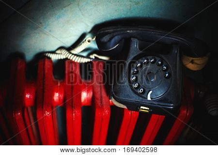 Old Telephone On Red Radiator
