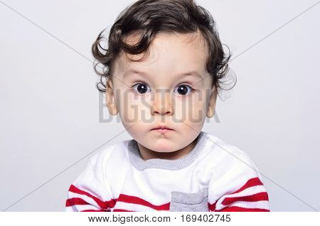 Portrait of a cute curly hair baby boy looking surprised.Adorable one year old child looking funny and curious. Baby boy with big eyes wondering.