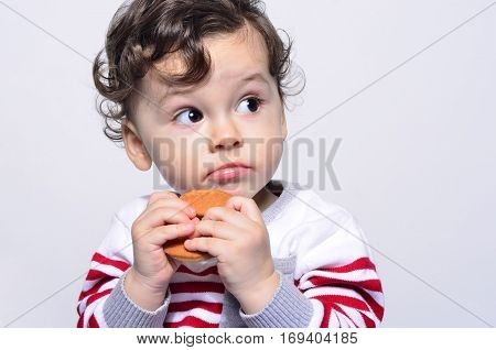 Portrait of a cute baby eating a biscuit looking up curious.One year old kid eating biscuits by himself. Adorable curly hair boy being hungry.