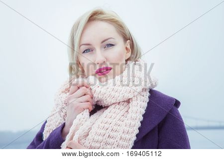 Girl with light hair wearing a big pink scarf and violette coat