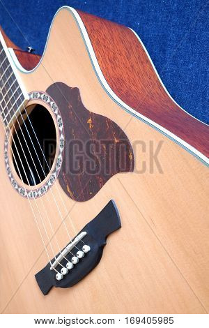 Classic acoustic six strings guitar natural color top from spruce with cutaway fragment on jeans background vertical view closeup