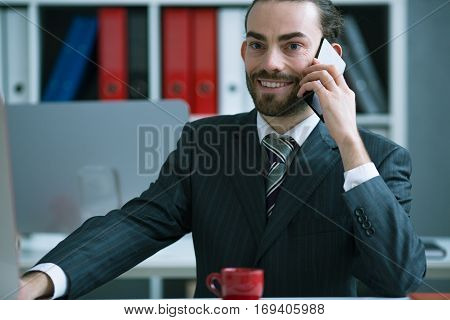 Satisfied businessman talking on the phone in the office